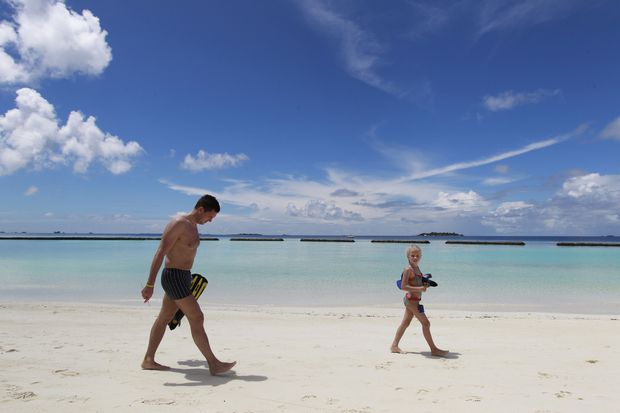 Touristen spazieren einen Strand auf einer der maledivischen Urlaubsinseln entlang.