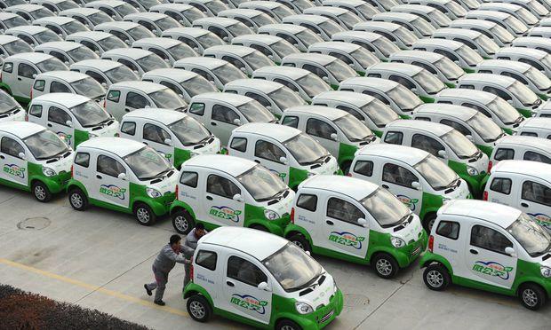 Arbeiter rollen ein E-Auto auf den Parkplatz einer Fabrik im chinesischen Changxing.