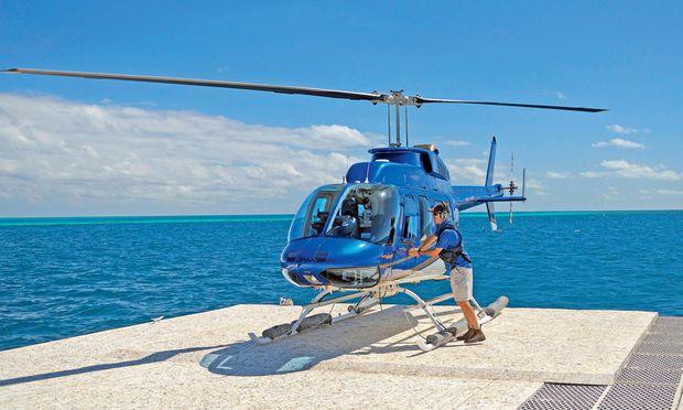 Lautstark. Ein Hubschrauber startet von einem Ponton zu Rundflügen über dem Riff.