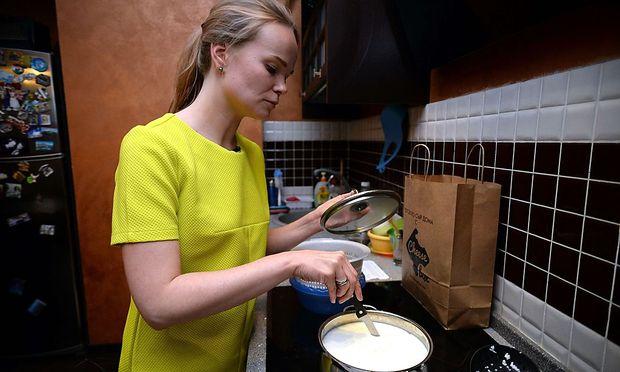 Eine Russin bereitet ihren eigenen Käse zu.