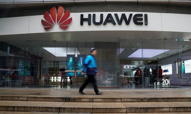 A man walks by a Huawei logo at a shopping mall in Shanghai