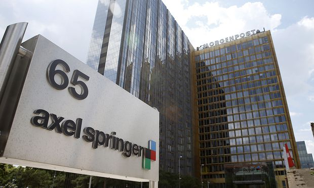 The logo of German publisher Axel Springer is pictured in front of the company's headquarters in Berlin