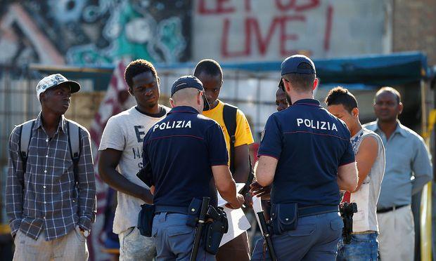 Italienische Beamte nehmen die Personalien von Migranten in Rom auf.