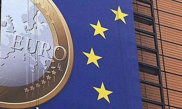 Workers display a giant banner on the European Commission headquarters showing a model of an euro coi