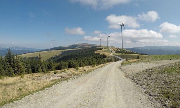 Eine Straße führt entlang der Kette von Windrädern; im Hintergrund das Stuhleck ohne Windräder