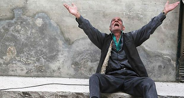 A man reacts at a site hit by what activists say was a barrel bomb dropped by forces loyal to Syria´s President Bashar al-Assad, in Aleppo´s al-Fardous district