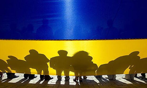 Menschen vor einer ukrainischen Flagge