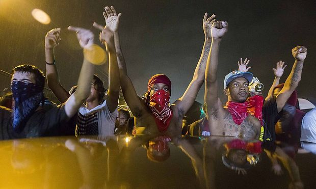 Protesters gesture as they stand in the street in defiance of a midnight curfew in Ferguson, Missouri