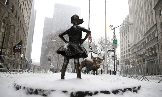 Snow falls on the The Fearless Girl statue facing the Charging Bull in a snow storm in New York City