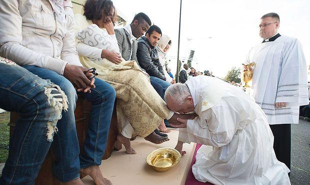 Mesmun mit ihrer Tochter Merhawit. Der Papst küsst der Eritreerin die Füße.