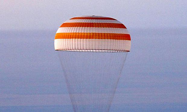 The Soyuz space capsule under a parachute flies before the landing in northern Kazakstan Friday, Sept