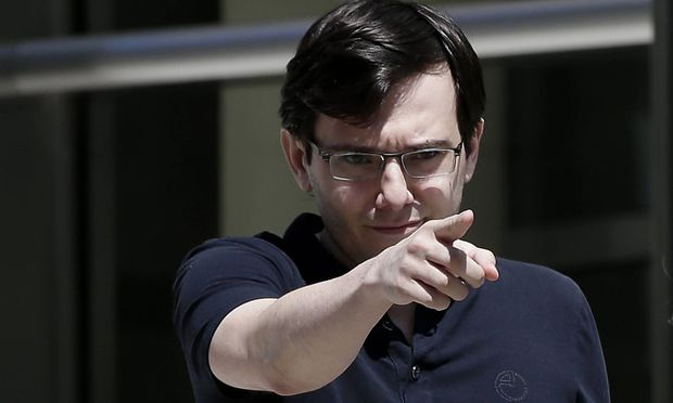 Former Turing Pharmaceuticals CEO Martin Shkreli points as he walks to the microphones to speak to t