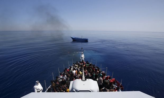 A group of 300 sub-Saharan Africans sit on board the Italian Finance Police vessel Di Bartolo as their boat  is left to adrift off the coast of Sicily