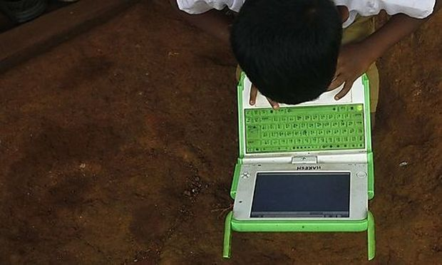 A school boy uses a laptop provided under the One Laptop Per Child project by a non-governmental or project by a non-governmental or
