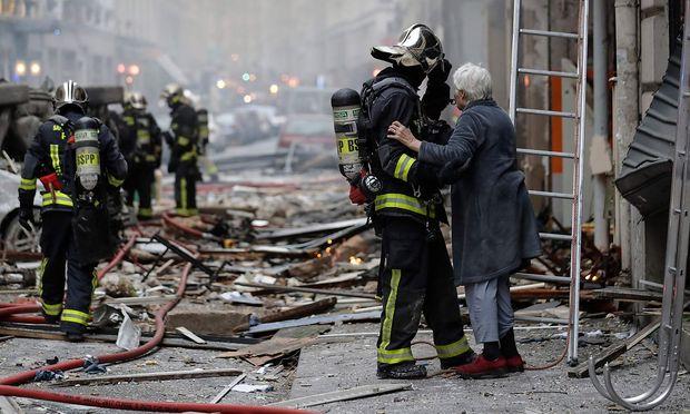 Feuerwehrmänner bergen eine Frau aus dem Gebäude.