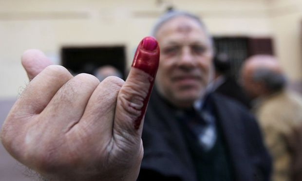 An Egyptian man shows his ink-stained finger after voting during a referendum on the new Egyptian constitution at a polling station in Cairo