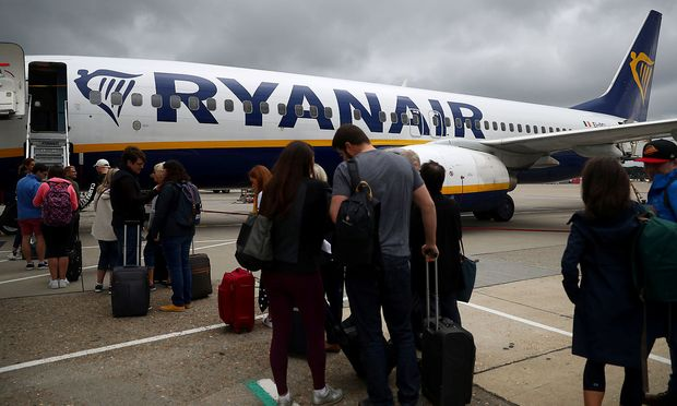 FILE PHOTO: Passengers wait to board a Ryanair flight at Gatwick Airport in London