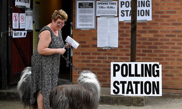 A woman with her dogs is pictured outside a polling station, where Britain's Prime Minister Theresa May voted in the European Parliament Elections, in Sonning