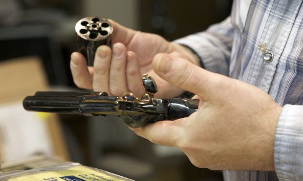 Chris Dogolo inspects a Colt Single Action Army revolver in Guilford