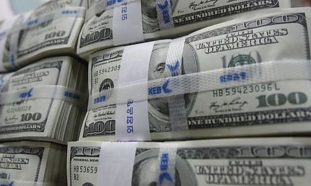 A bank employee counts U.S. dollar notes during a photo opportunity at a bank in Seoul