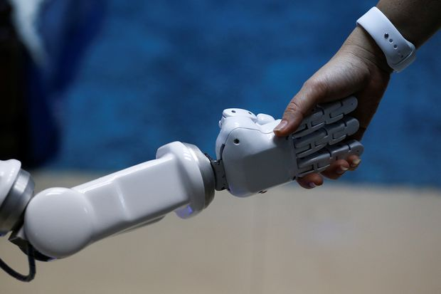 Chalermpon Punnotok, CEO of CT Asia Robotics gives a hand to a robot during an interview with Reuters in Bangkok