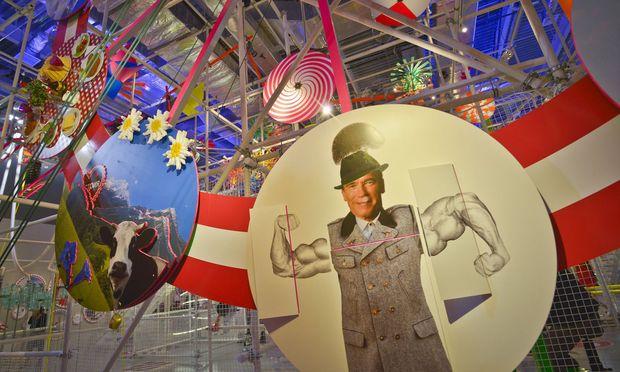 Riesenrad mit österreichischen Kitschsymbolen: Sisi, Sachertorte, Schwarzenegger.