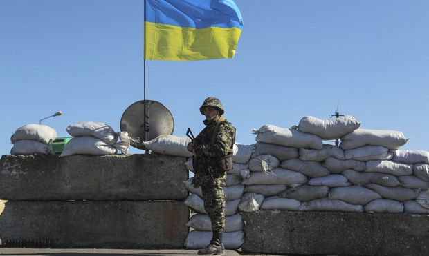 A Ukrainian serviceman stand  guard at a checkpoint near the town of Armyansk
