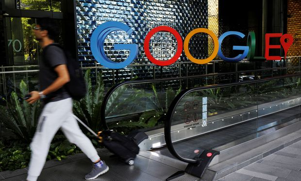 A man passes a Google signage outside their office in Singapore