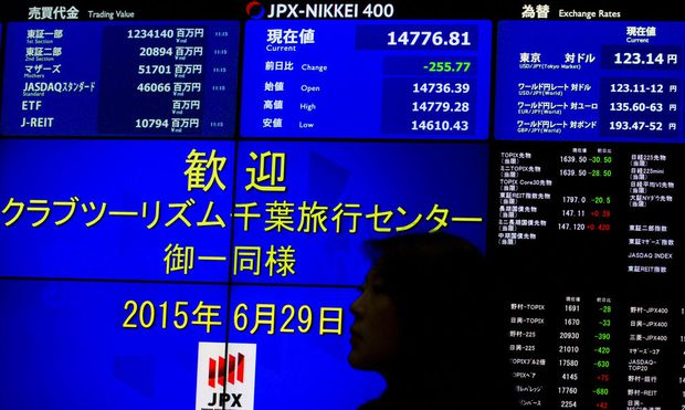 Woman stands in front of display showing market indices at Tokyo Stock Exchange in Tokyo