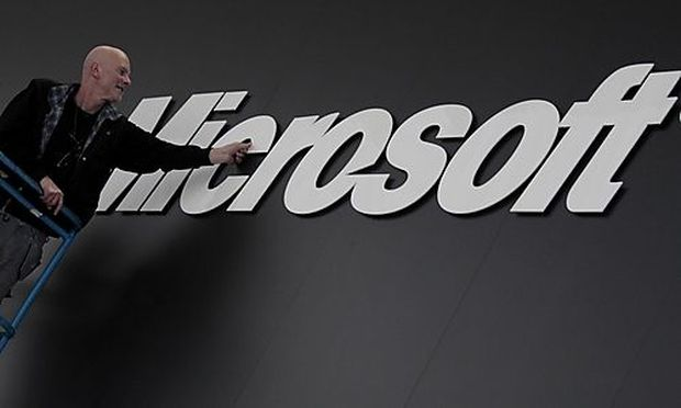 A worker prepares the logo on the Microsoft stand on the CeBIT computer fair in Hanover