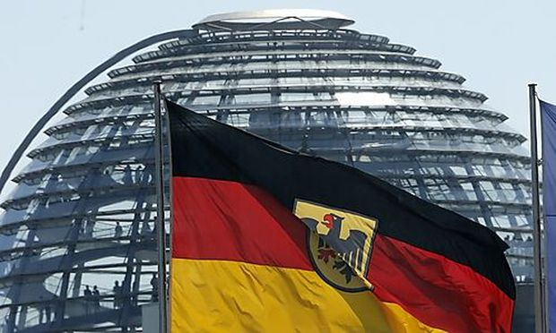 The German and the European Union flags are pictured in front of the cupola on top of the Reichstag building in Berlin