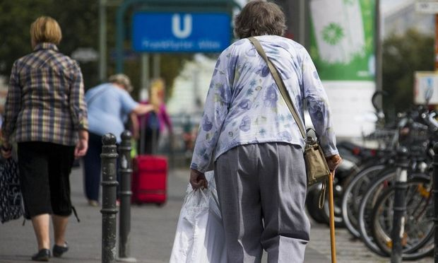 Elderly woman walks on stick along shopping street in Berlin