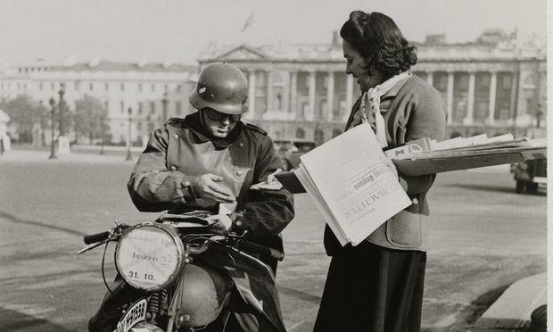 """Ein deutscher Soldat kauft 1940 in Paris einen """"Völkischen Beobachter""""; Franzosen übersetzten den Zeitungstitel gern mit """"L'Observateur raciste"""". Schon im 19. Jahrhundert war der Begriff """"völkisch"""" untrennbar mit radikalem Nationalismus und Rassendenken verknüpft."""