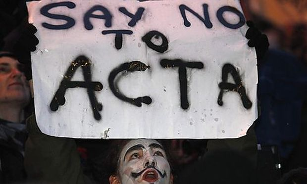 A demonstrator protests against Polands government plans to sign ACTA, in front of the European Unio