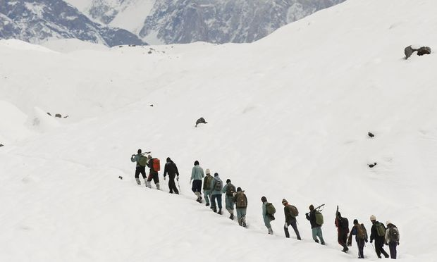 A group of Pakistani soldiers carry their guns uphill along the K2 base camp trek in the Karakoram mountain range in Pakistan