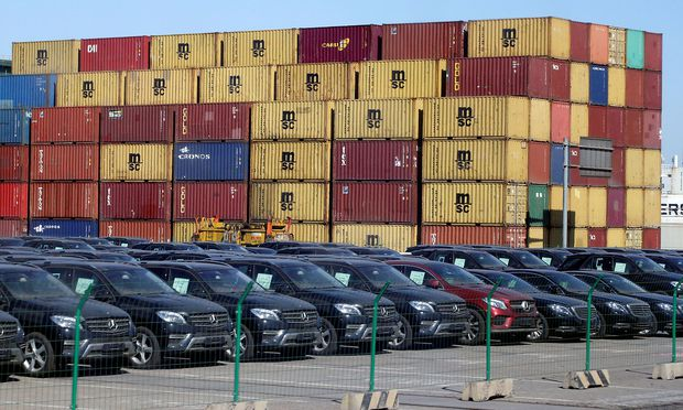 FILE PHOTO: Imported Mercedes Benz cars are seen next to containers at Tianjin Port