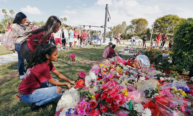 Bouquets are placed at a memorial on campus on the one year anniversary of the shooting which claimed 17 lives at Marjory Stoneman Douglas High School in Parkland