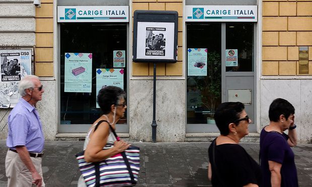People walk past a Carige bank in Rome