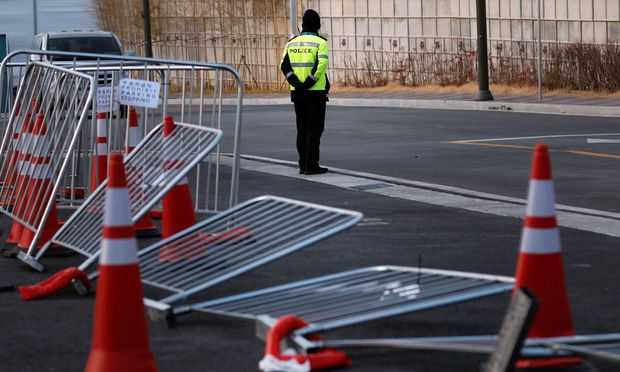 A policeman stands next to a barricade which fell over due to high winds outside Gangneung Hockey Centre, in Gangneung