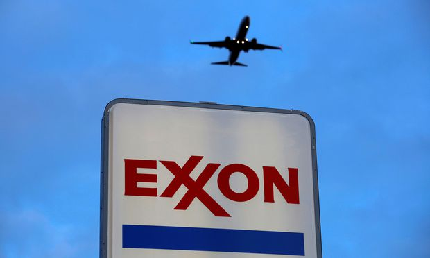 An airplane comes in for a landing above an Exxon sign at a gas station in the Chicago suburb of Norridge