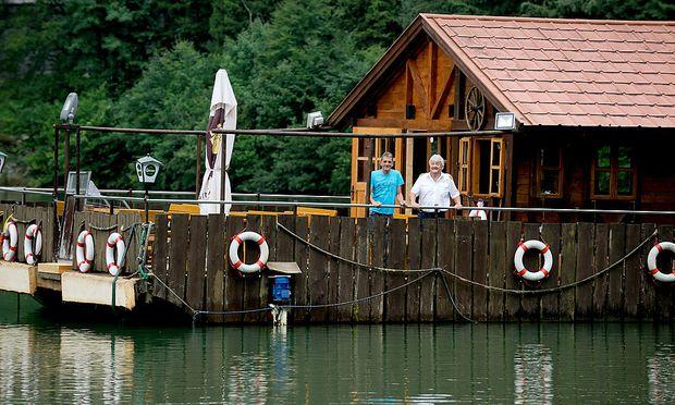 Wirt Helmut Pölz (links) und Kapitän Franz Eder auf ihrer schwimmenden Hütte auf dem See.