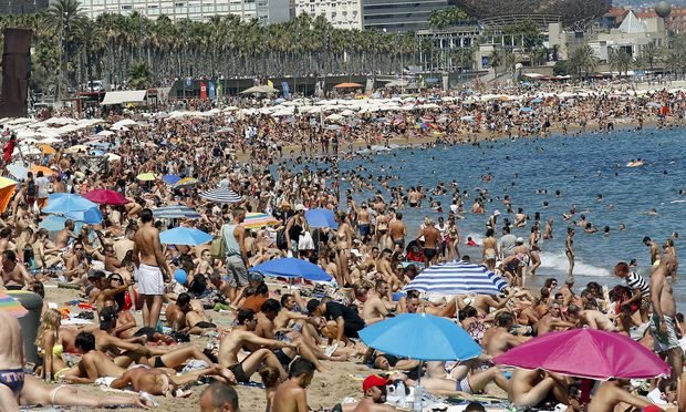 People cool off at Sant Sebastia beach in Barceloneta neighbourhood in Barcelona