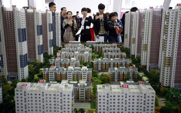 A sales assistant talks to visitors in front of models of apartments at a real estate exhibition in Shenyang