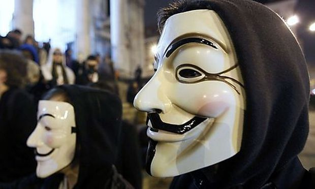 A protester wearing a Guy Fawkes mask, symbolic of the hacktivist group Anonymous, takes part in a