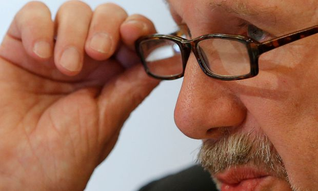 ECB Governing Council member Nowotny adjusts his glasses during a news conference in Vienna