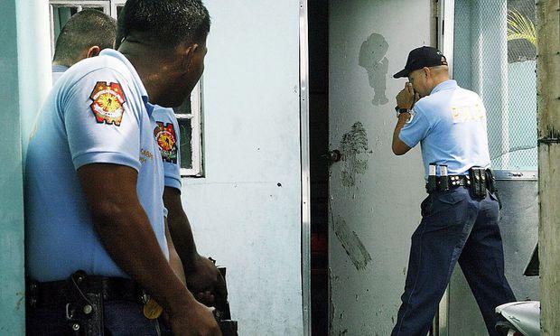 Die Polizei vor dem Haus des Verdächtigen in Manila auf den Philippinen.