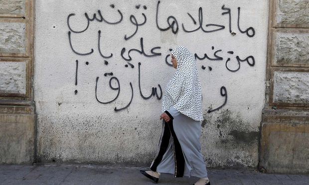 A woman walks past graffiti in Tunis