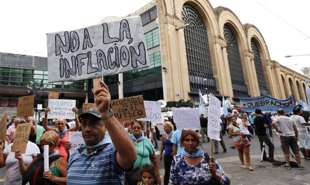 A demonstrator holds up a sign during a protest outside a Coto supermarket in Buenos Aires