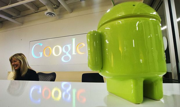A Google Android figurine sits on the welcome desk as employee McNeilly smiles at the new Google office in Toronto