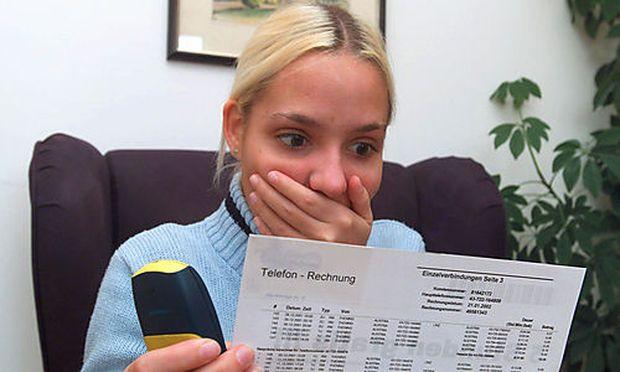 Junge Frau erschrickt ueber hohe Telefonrechnung